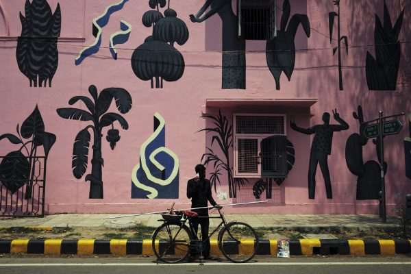 color street photography of a man against pink wall in New Dehli, India by Michael Westermann