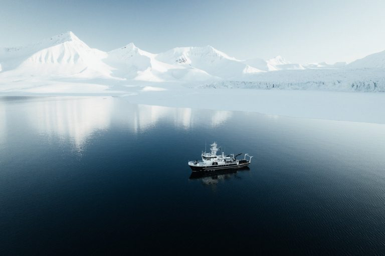 Landscape photo by Hannes Becker, glaciers, mountains, ship, fjord, Svalbard, Norway.