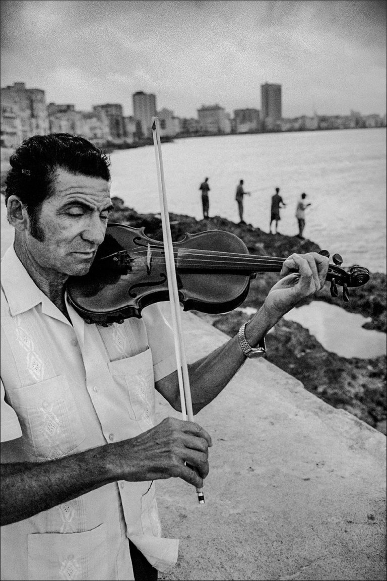 Black and white photo by Xavier Roy. Man playing violin, Havana, Cuba