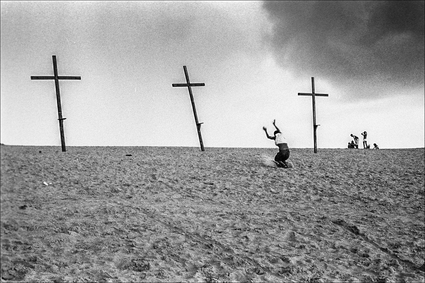 Black and white photo by Xavier Roy, man kneeling before three crosses, Lencois, Brésil 2002