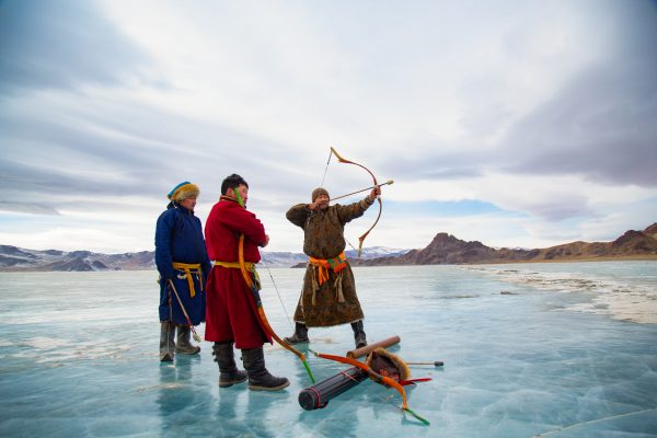 Color photograph of Mongolian men on frozen lake by Alessandra Manzotti