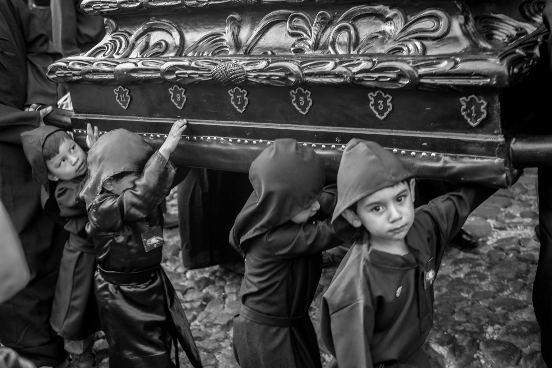 Black and white photo by Xavier Roy, young boys carrying coffin, Antigua, Guatemela