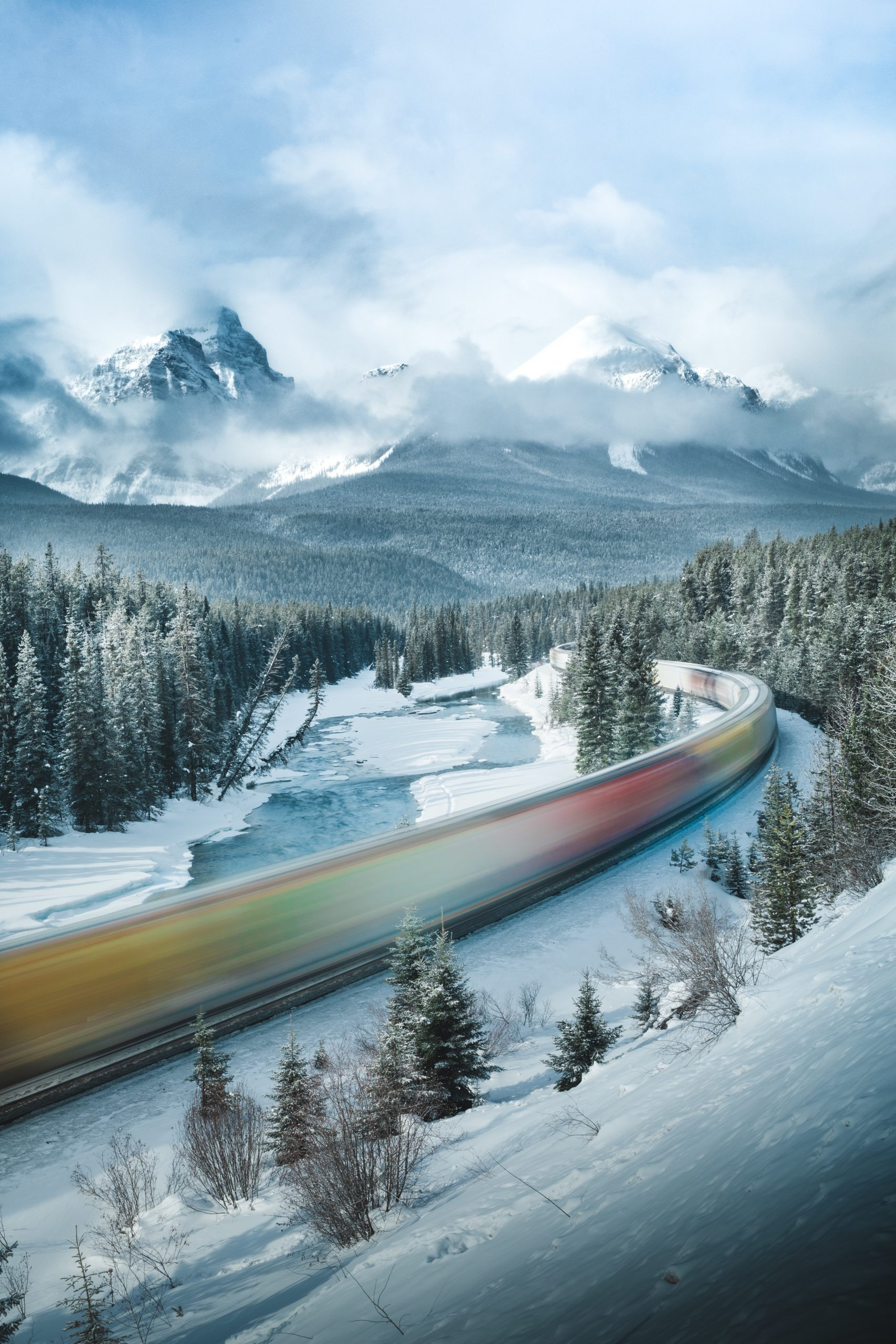 Landscape color photograph of a train in Alberta rocky mountains, canada by Benjamin Glassco