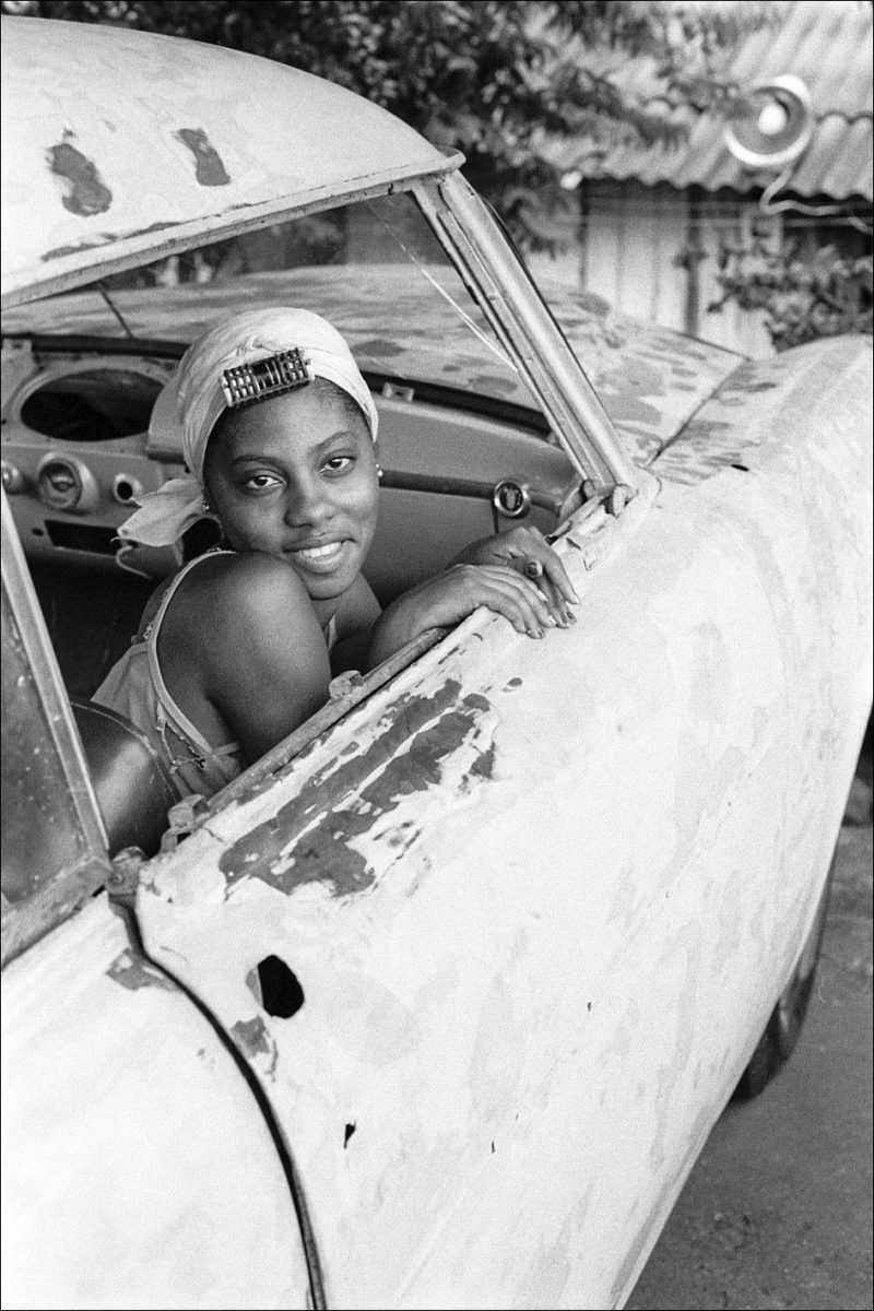 Black and white photo by Xavier Roy, portrait of woman in car, Havana, Cuba 2002