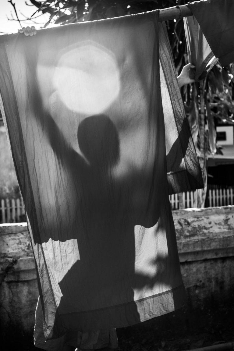 Black and white photo by Xavier Roy. Women hanging washing, Luang Prabang, Lao