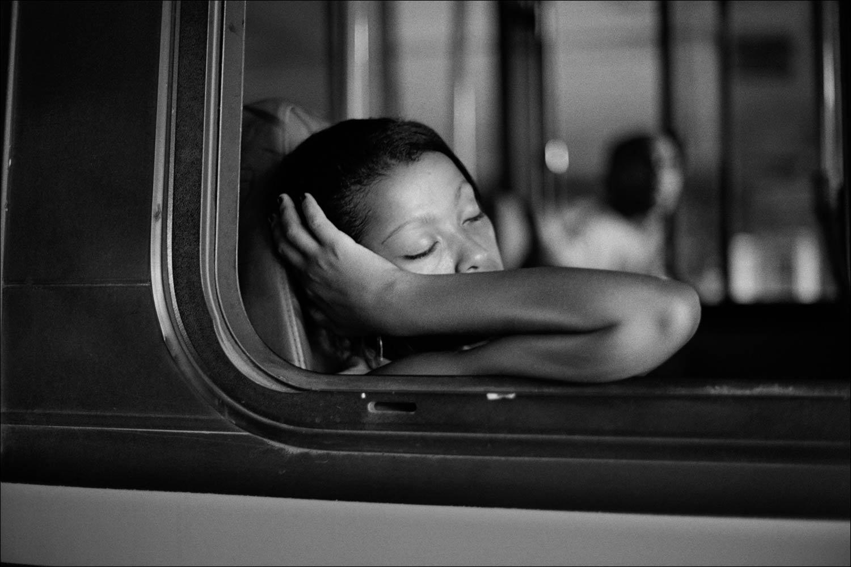 Black and white photo by Xavier Roy. Girl sleeping on bus, Rio de Janeiro, Brazil