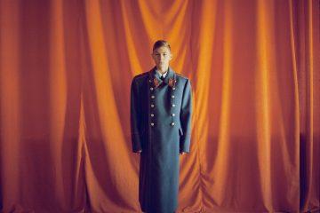 Retrato en color de un niño con uniforme militar por Michal Chelbin